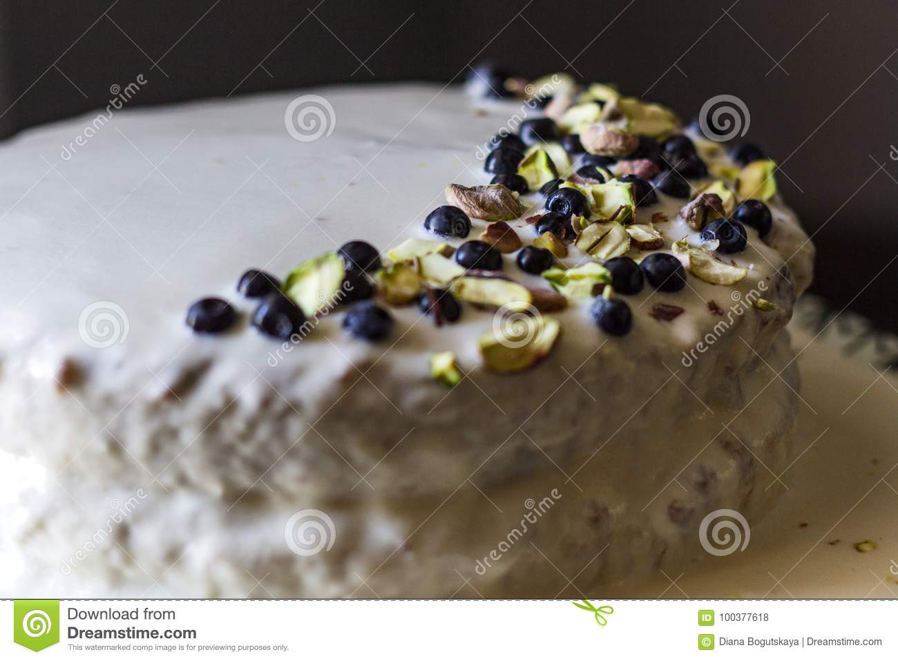 Homemade cake with white buttery cream with ornament from blueberries berries and pistachio on a dark background.