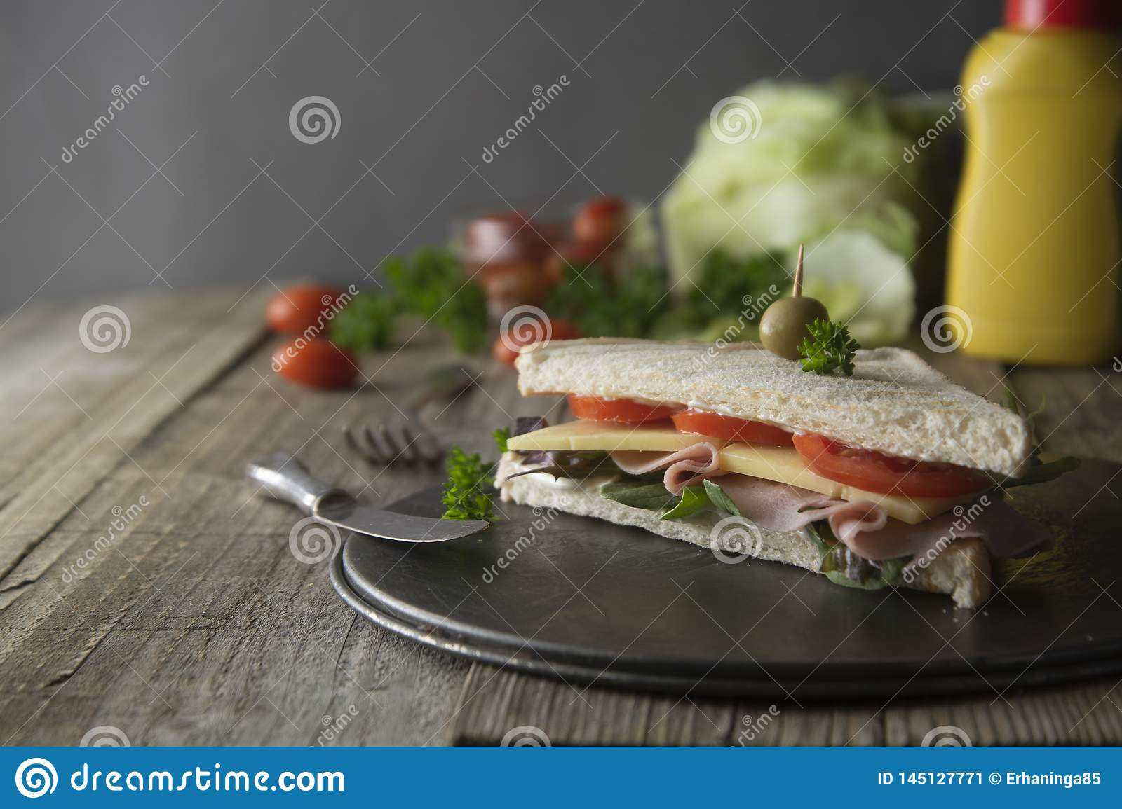 Homemade club sandwich. Toasted white bread triangles with ham, cheese fresh vegetables. Wooden table