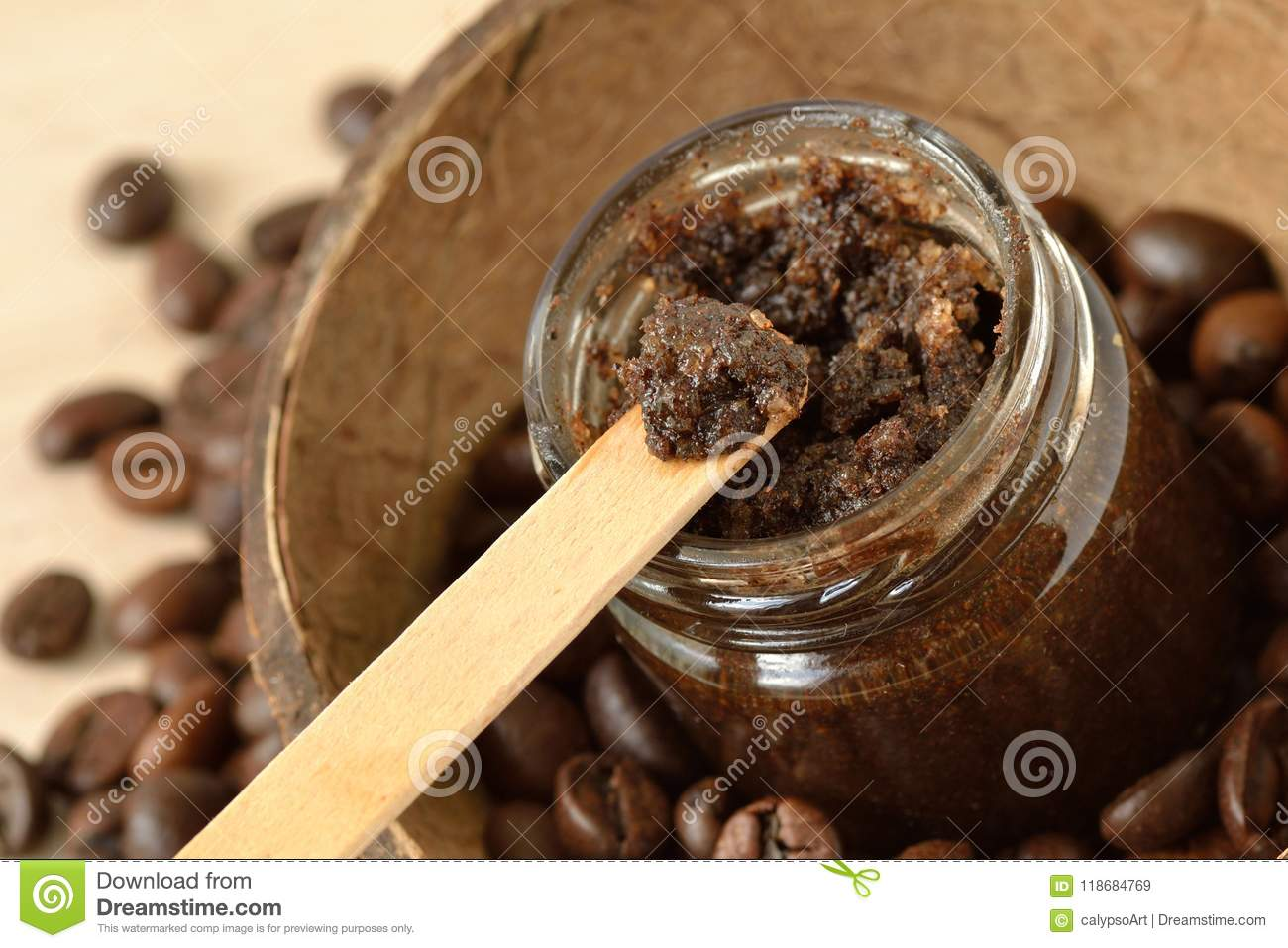 Homemade coffee scrub in a glass jar over coconut shell and coffee beans