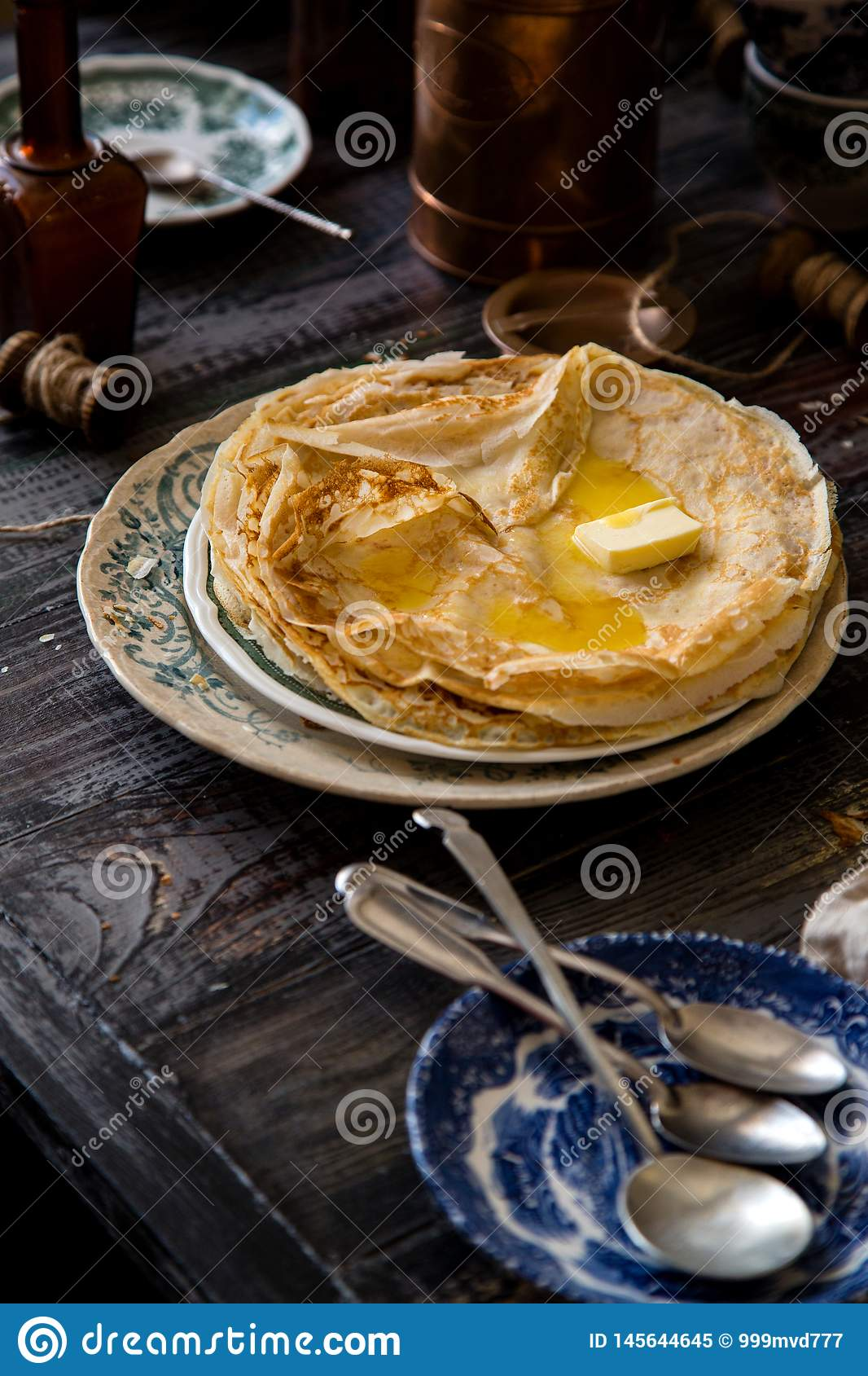 Homemade crepes with melted butter on vintage plate with green ornament stand on rustic grey table