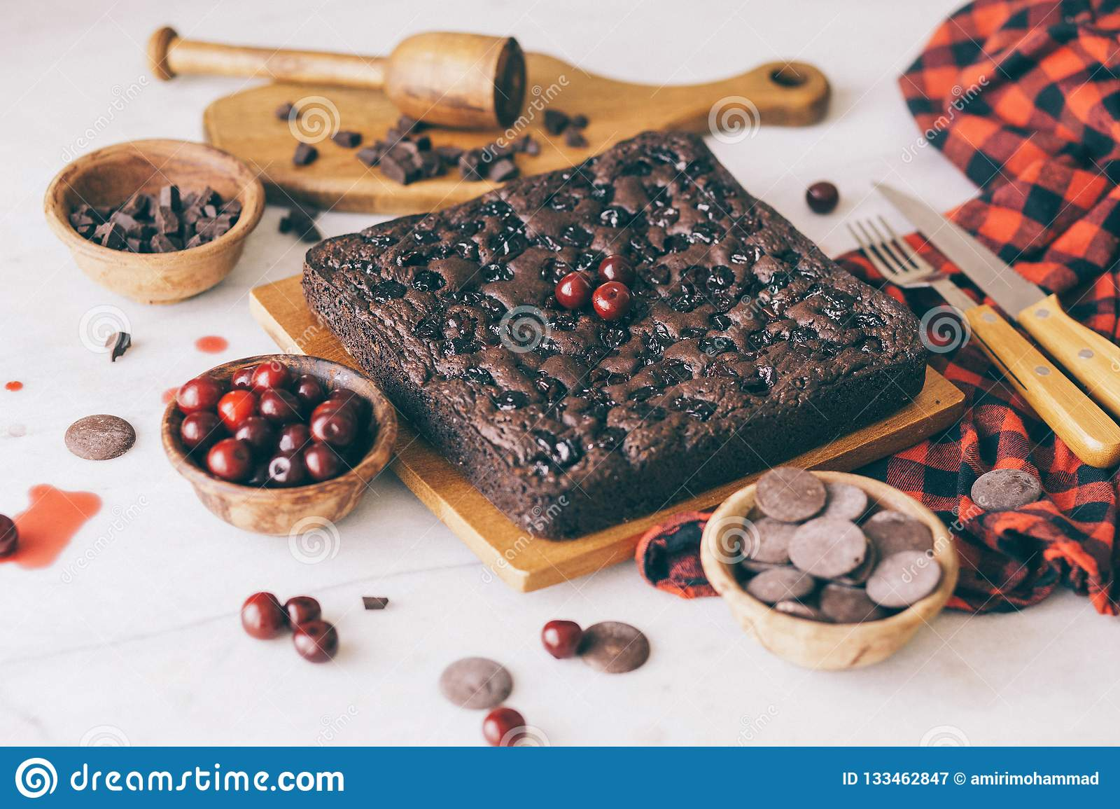 Homemade dark chocolate cherry brownie cake and sweet fresh cherries and delicious chocolate pieces in soft-focus.