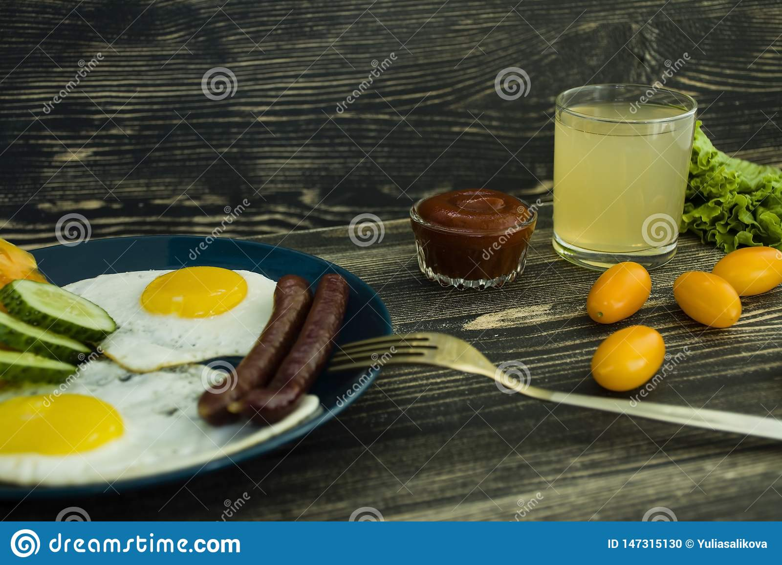 Homemade delicious breakfast with sunny side up fried egg, sausage, tomatos in top view