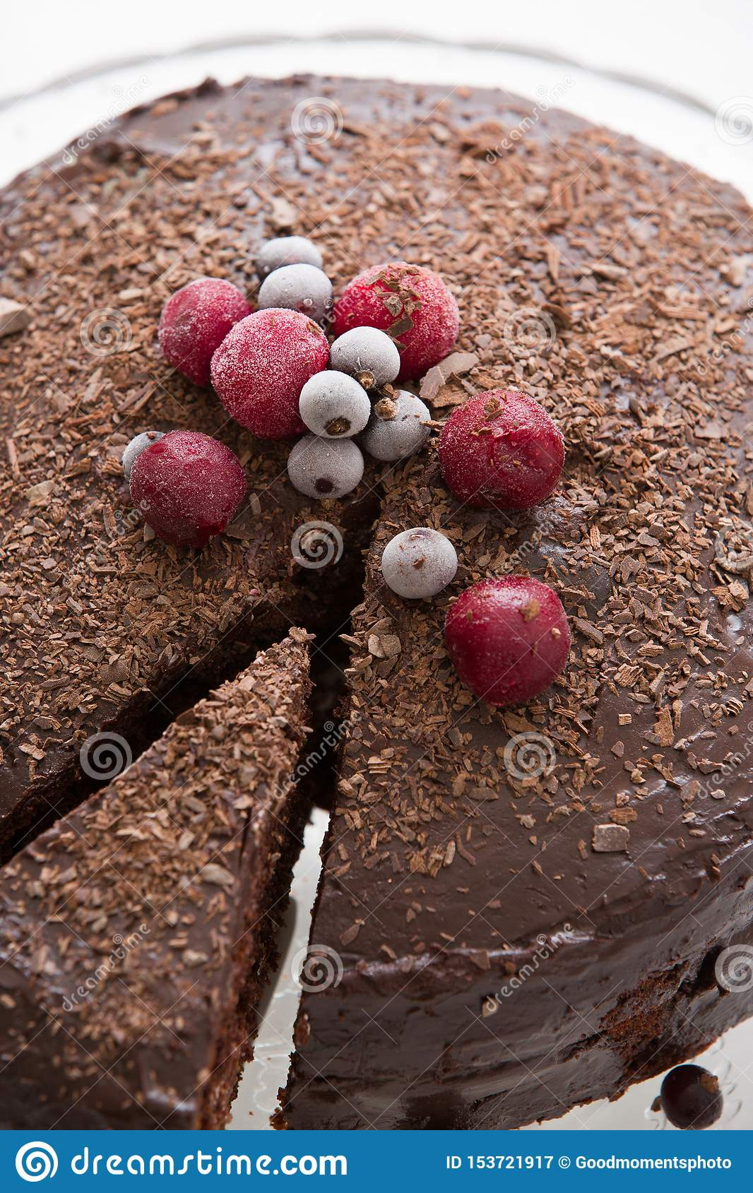 Homemade fresh chocolate birthday cake with organic frozen berries and chips on the top. Piece of cake and celebration