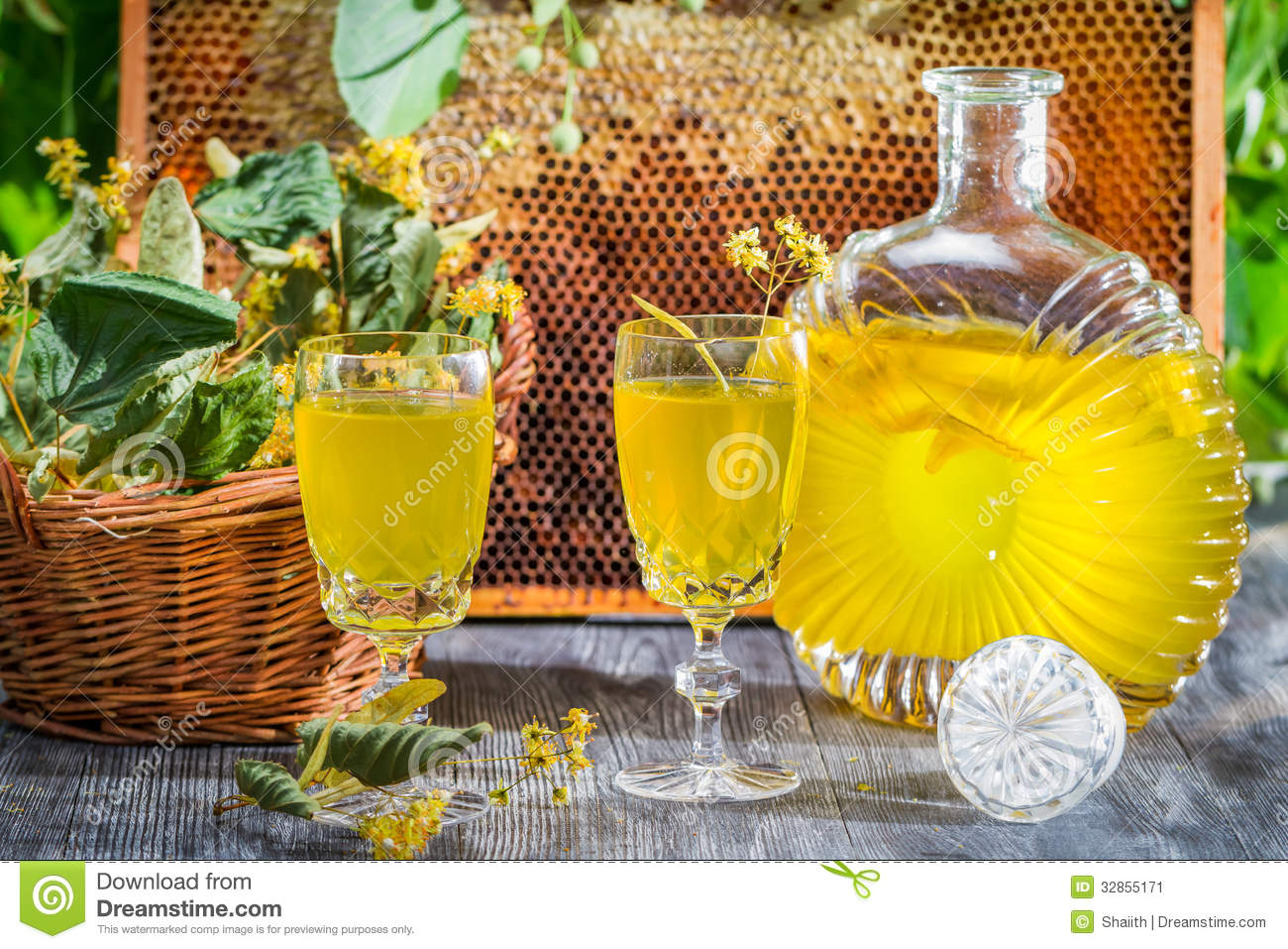 Homemade liqueur made of honey and lime on old wooden table.