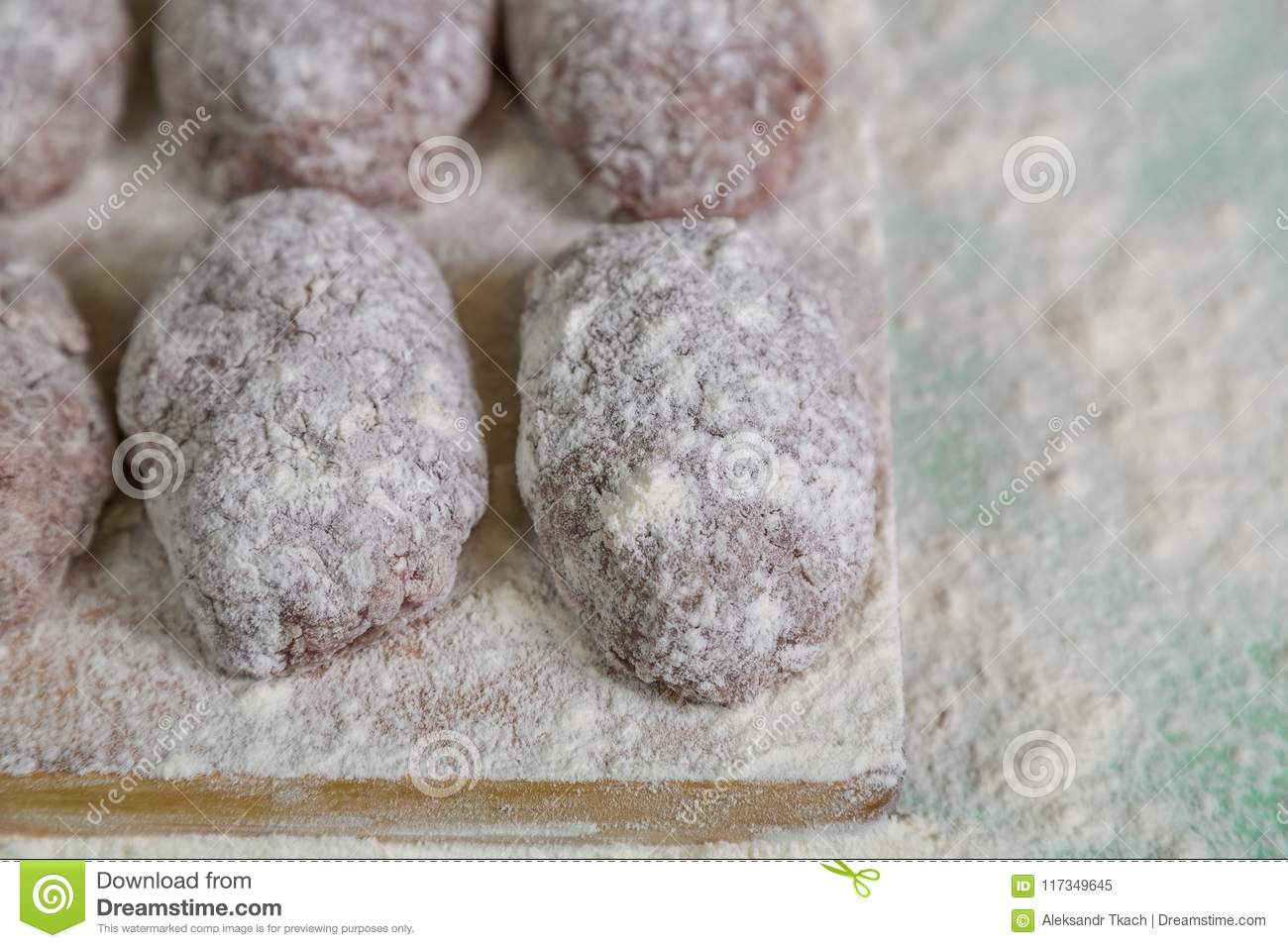 Homemade meatballs in flour on cutting Board prepared for roasting