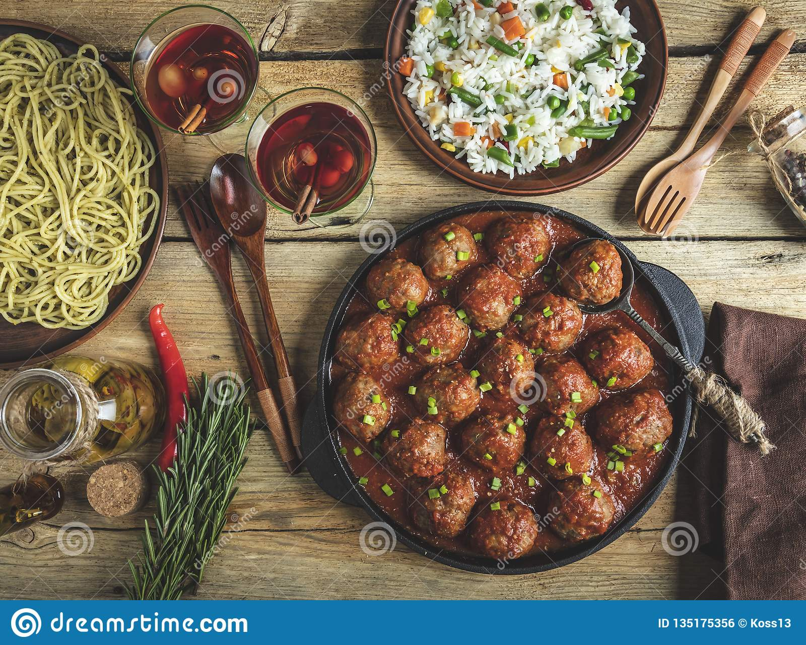 Homemade meatballs in tomato sauce. Frying pan on a wooden surface, rice with vegetables, pasta
