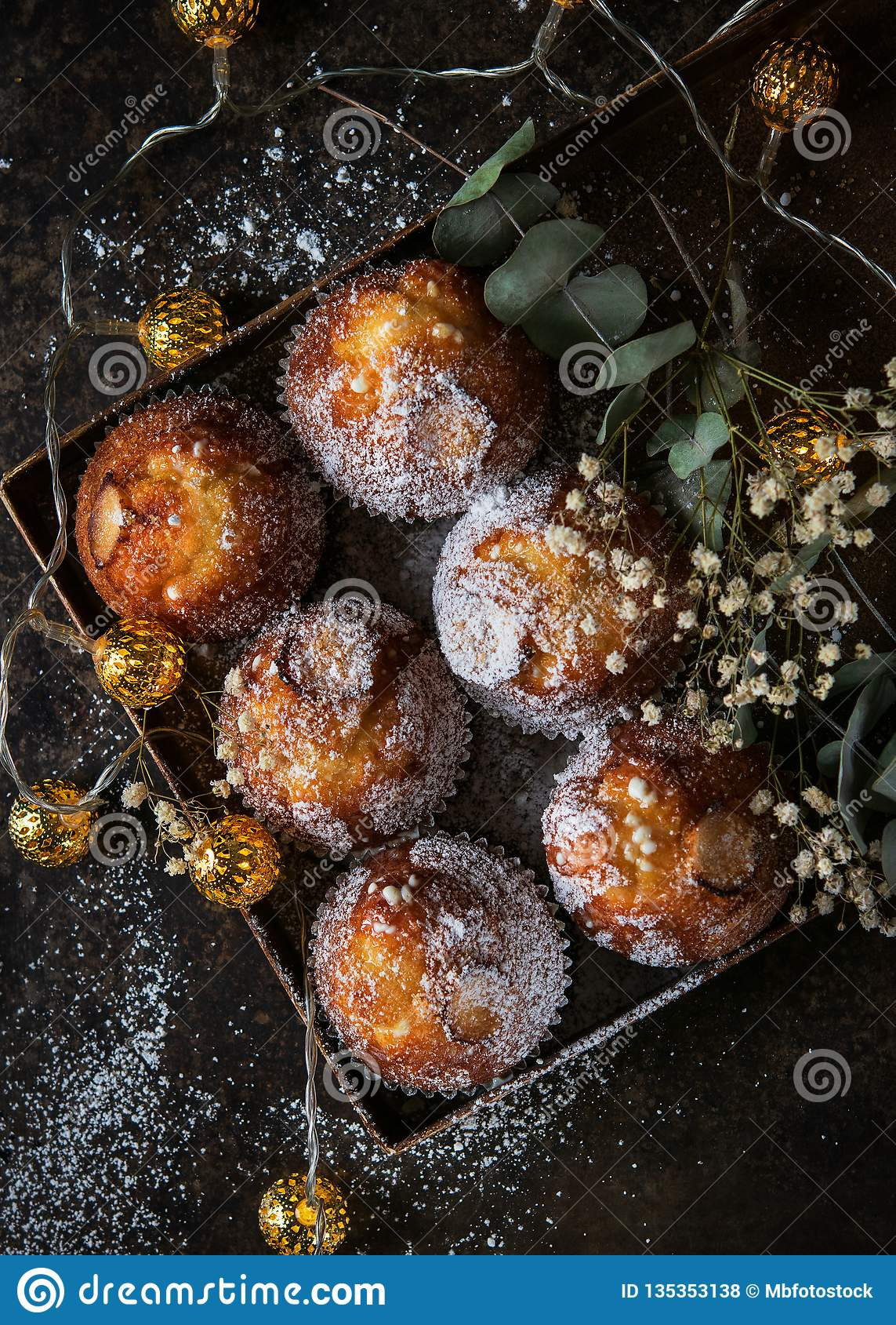 Homemade muffins with powdered sugar on a dark background, selective focus. Romantic concept