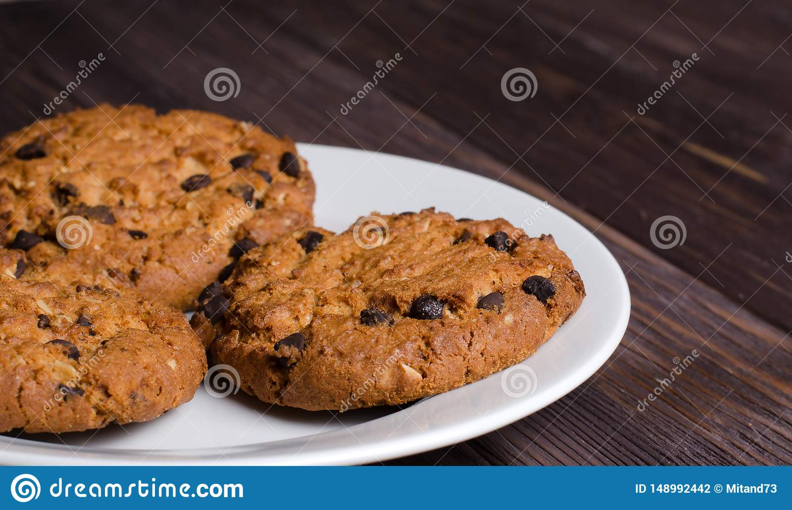 Homemade oatmeal cookies on a white plate. Wooden background