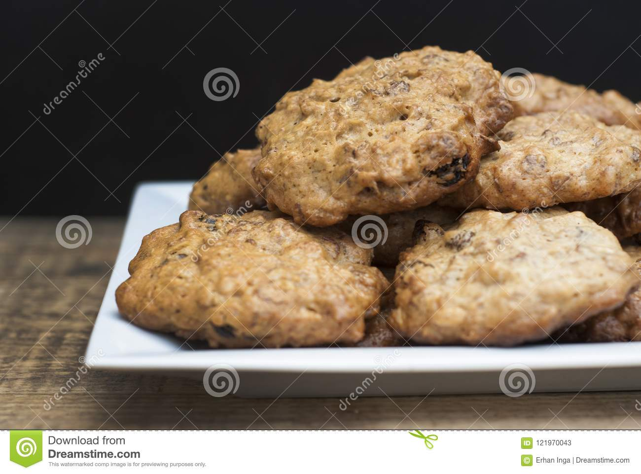 Homemade oatmeal cookies in white square plate,on wooden board and Black background. Sweet dessert snack, Healthy Food. Copy space