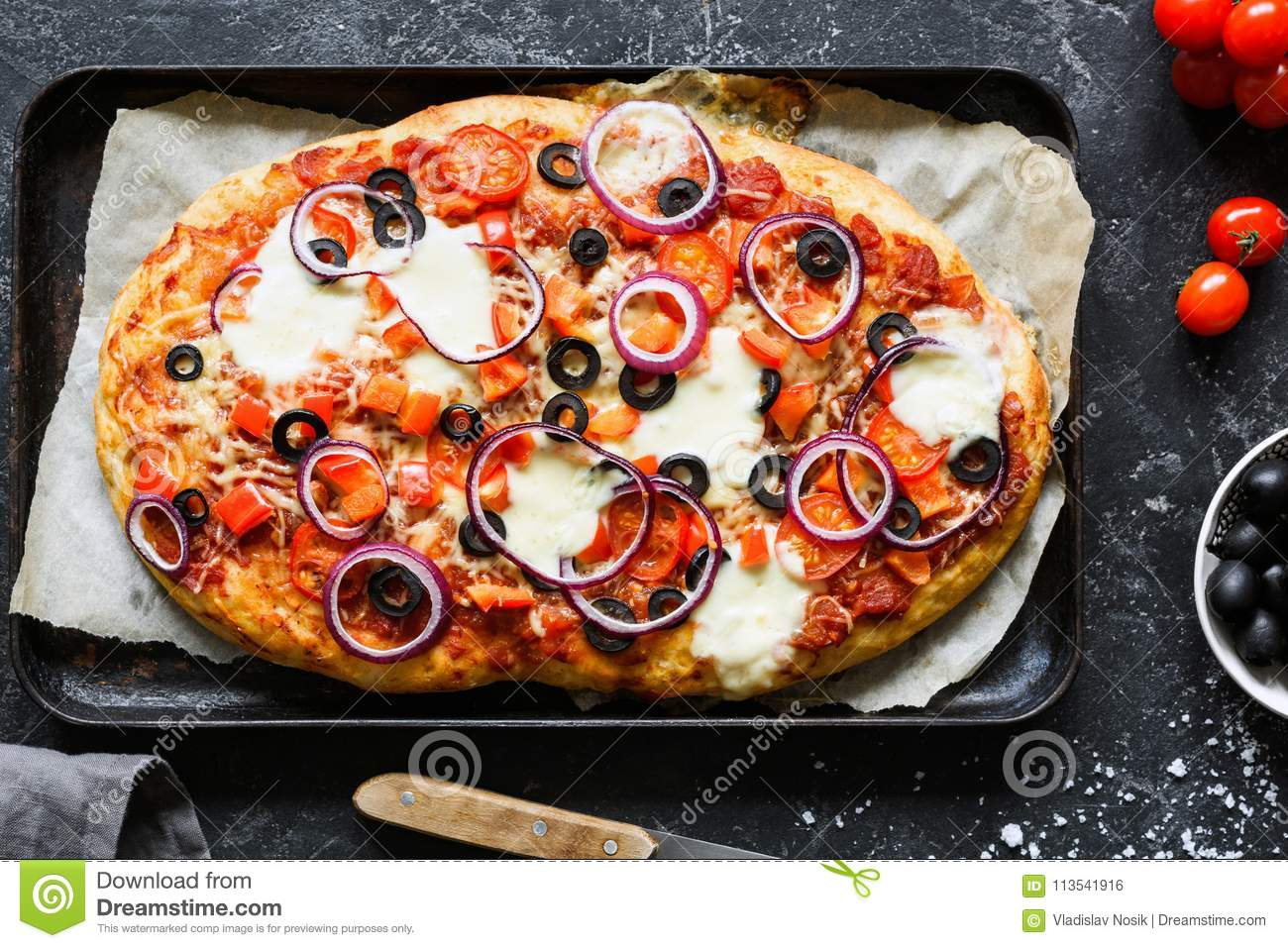 Homemade pizza with black olives, onion, tomato sauce, pepper and cheese on baking sheet