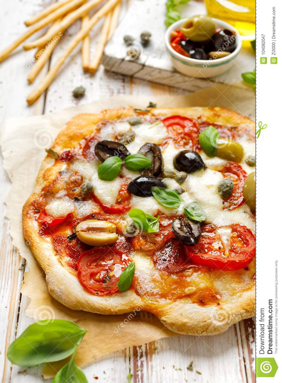 Homemade pizza with tomatoes, olives, salami, mozzarella cheese and fresh basil on a wooden rustic table