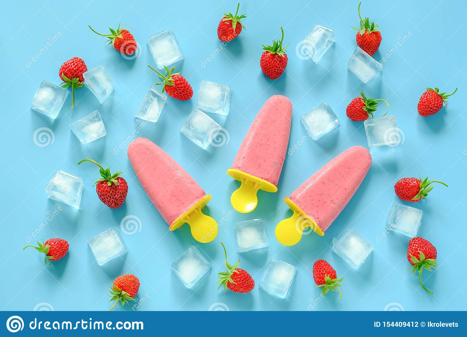 Homemade popsicles. Natural ice cream in bright plastic molds, strawberries and ice cubes on blue background. Top view Flat lay