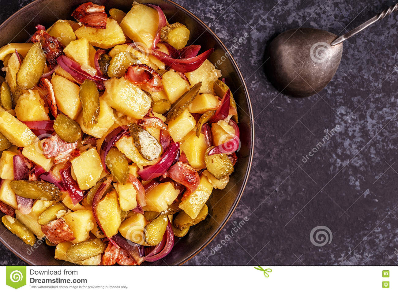 Homemade potato salad with bacon and pickles.