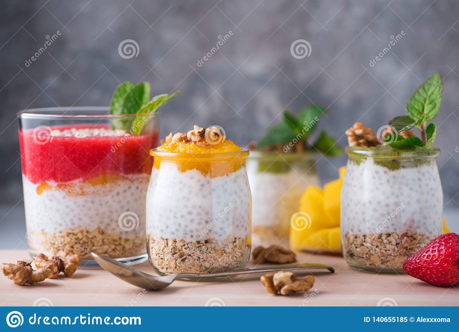 Homemade pudding of Chia seeds and almond milk with cereals and puree of kiwi, strawberry and mango with walnuts and mint in glass