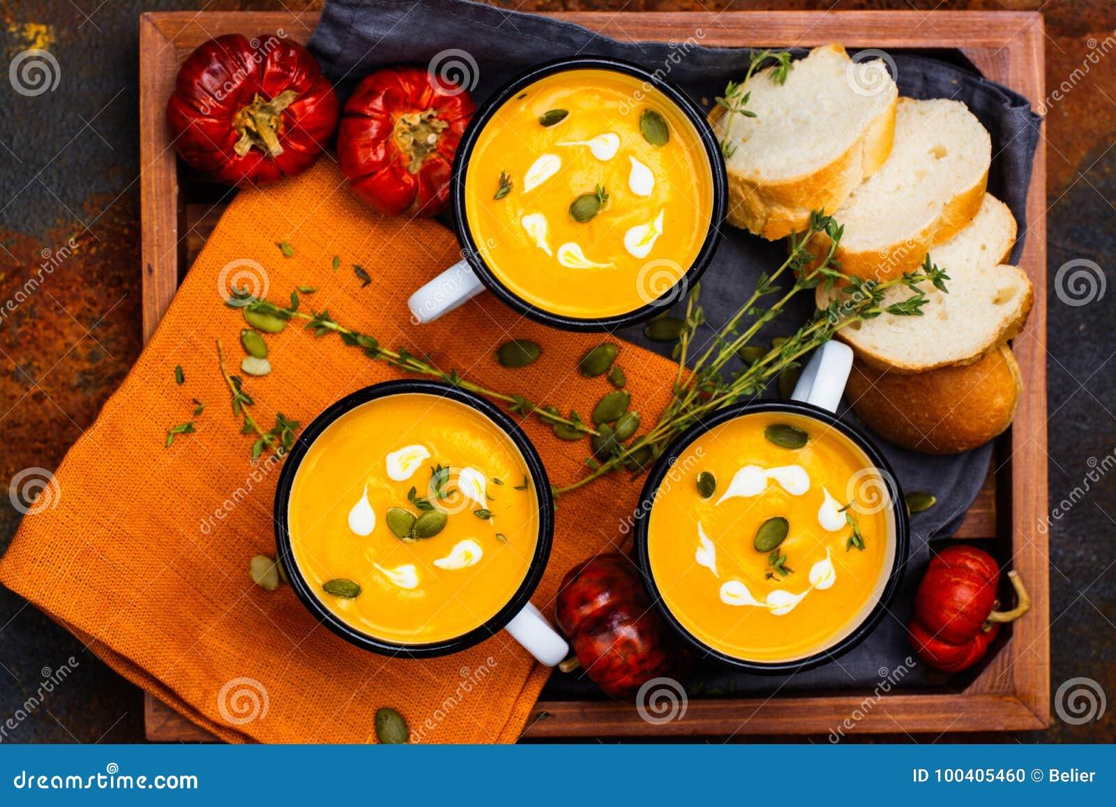 Homemade pumpkin soup in retro enamel mugs