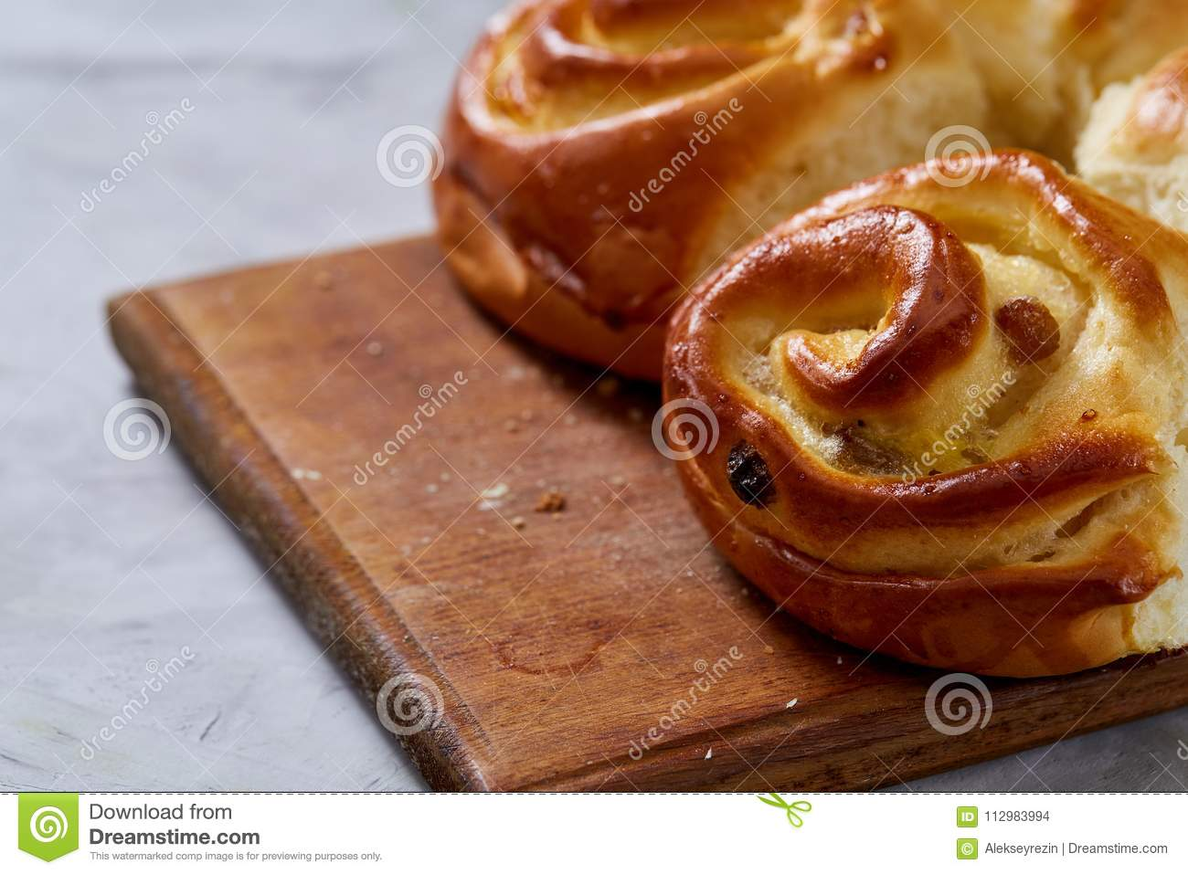 Homemade rose buns on wooden cutting board over white textured background, close-up, shallow depth of field
