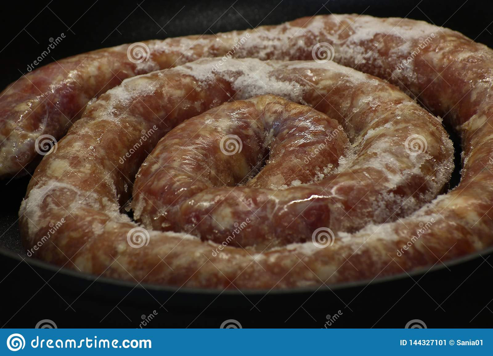 Homemade sausage, twisted meat is formed in the form of a long sausage. finger shoved sausage. simple meal. wrapped with a ring