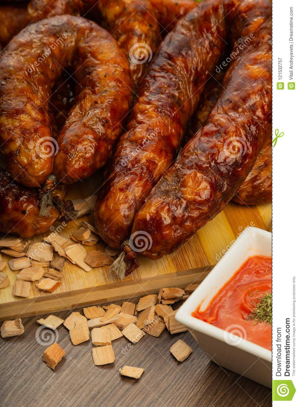 Homemade sausage on a wooden background with seasonings and sauce