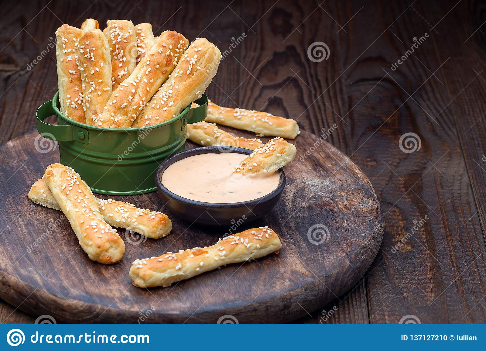 Homemade savory bread sticks with cheese and sesame in a basket, served with sauce on wooden board, horizontal, copy space