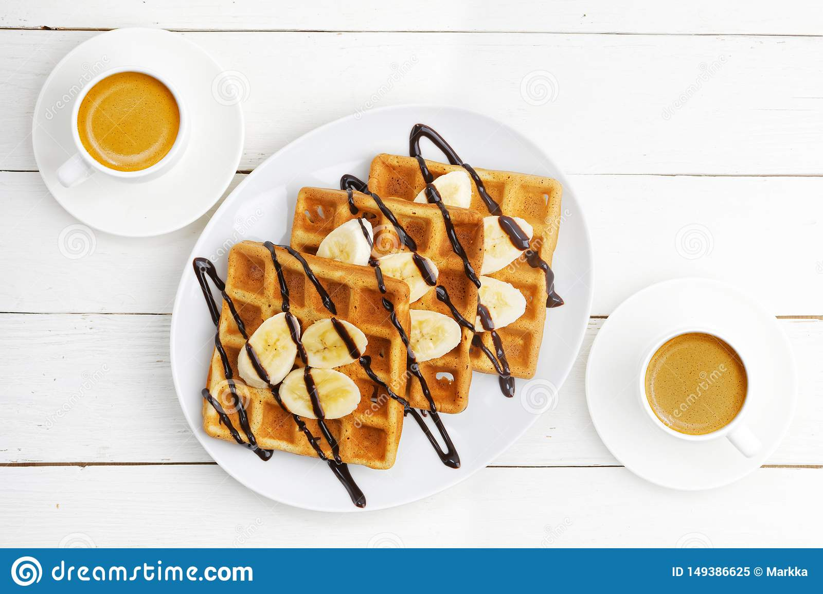 Homemade soft waffles with banana slices topped with chocolate and two cup of coffee on white wooden table