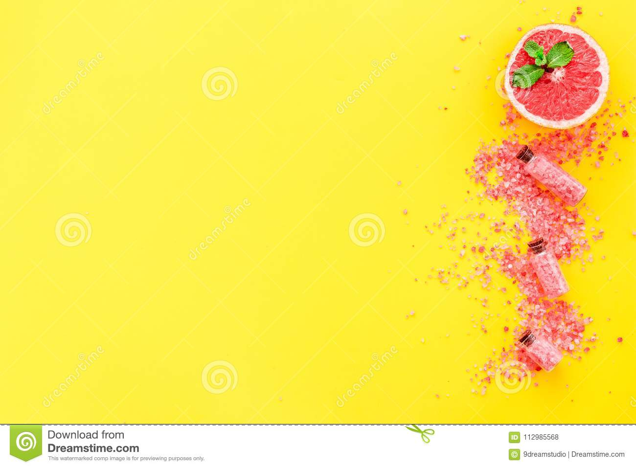 Homemade spa with grapefruit salt in natural cosmetic set fruit yellow background top view mock up