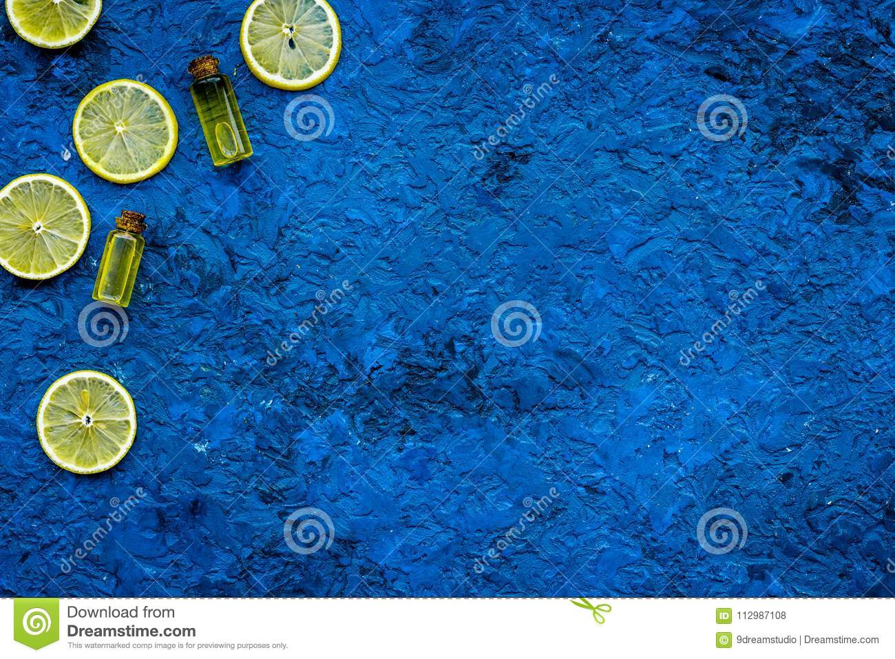 Homemade spa with lemon oil in natural cosmetic set on blue background top view space for text