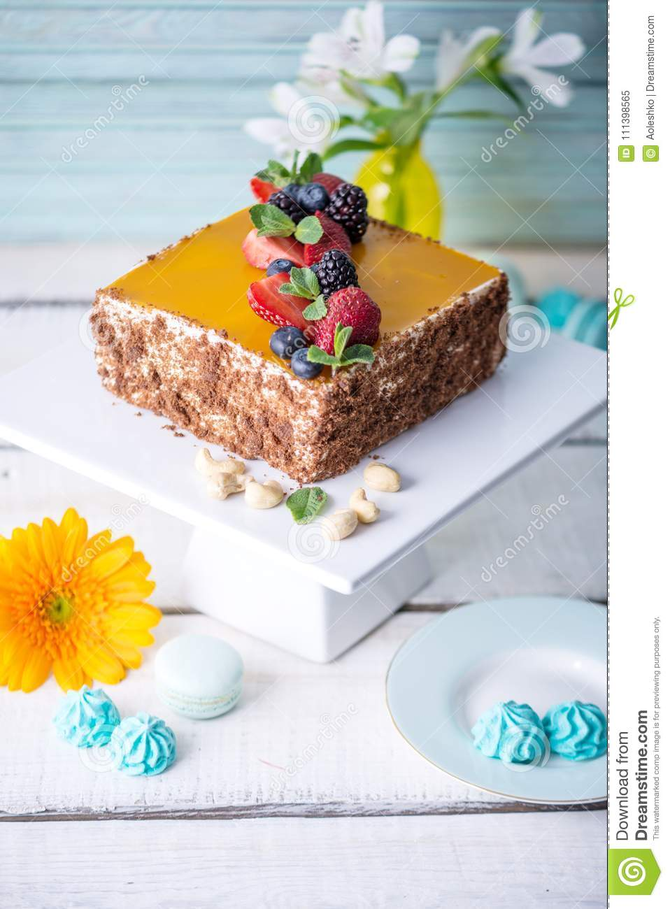 Homemade square cake decorated on top of yellow jelly and berries with mint on light background.