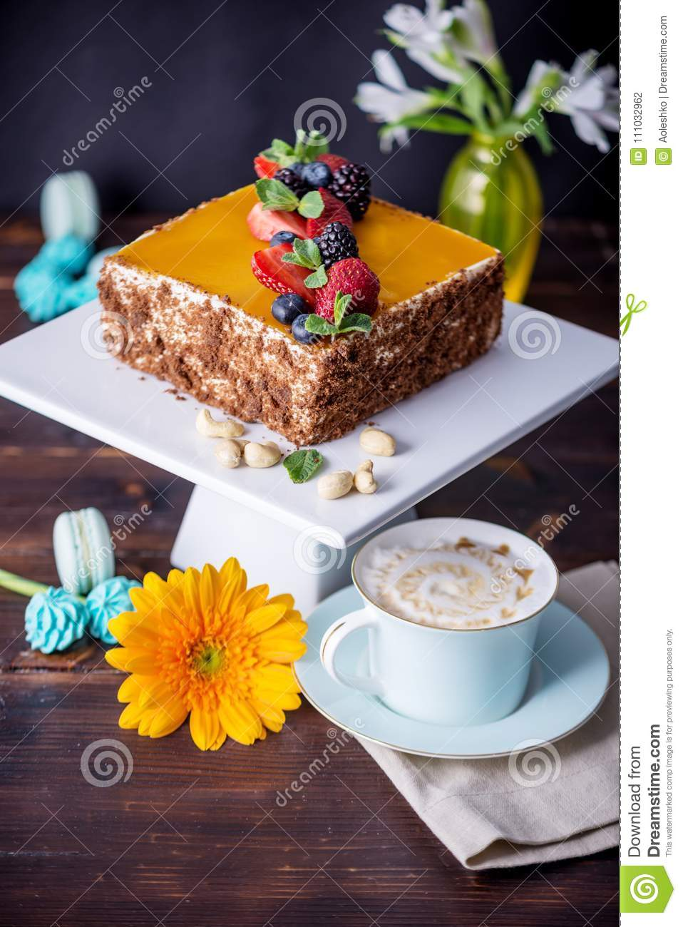 Homemade square cake decorated with yellow jelly on top and berries with mint on dark background