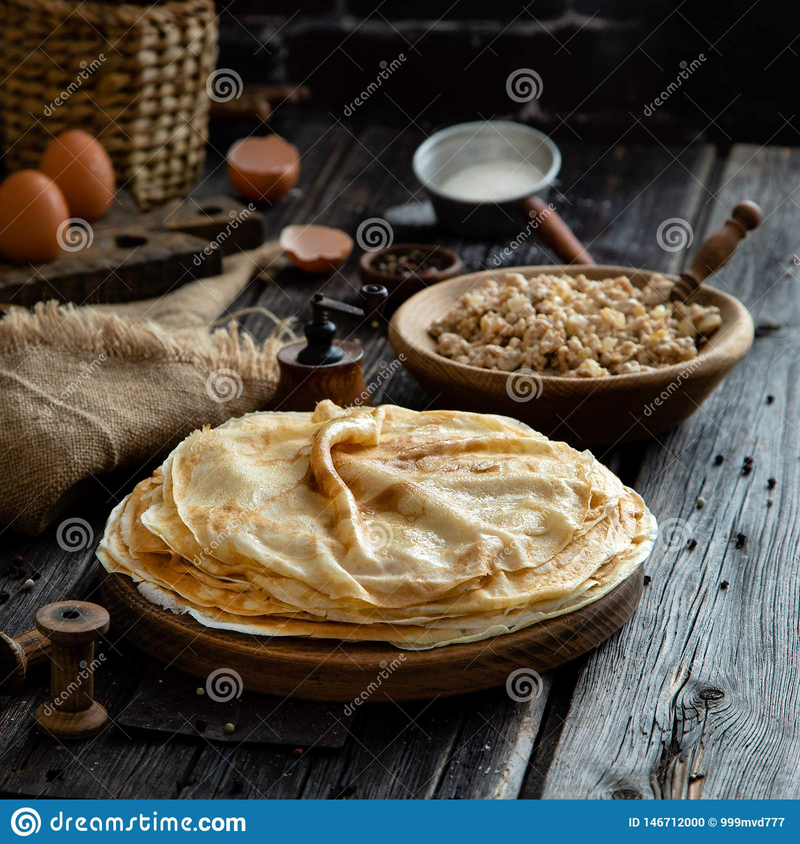 Homemade stack of crepes on wooden plate stand on rustic table with plate of ground fried beef