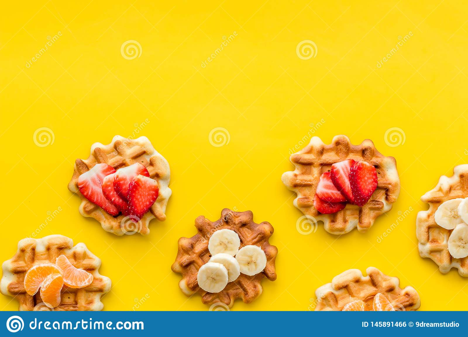 Homemade Viennese waffles with strawberry, tangerine and banana topings on yellow background top view make-up. Sweet breakfast. Homemade Viennese waffles with royalty free stock image