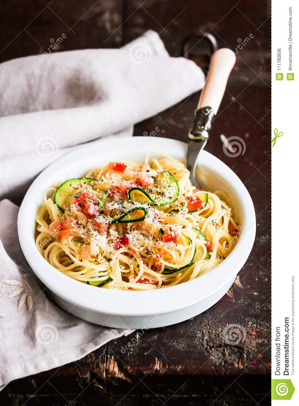 Homemade whole wheat spaghetti pasta with ripe tomatoes, caramelised courgette or zucchini, freshle grated parmesan cheese in a bo