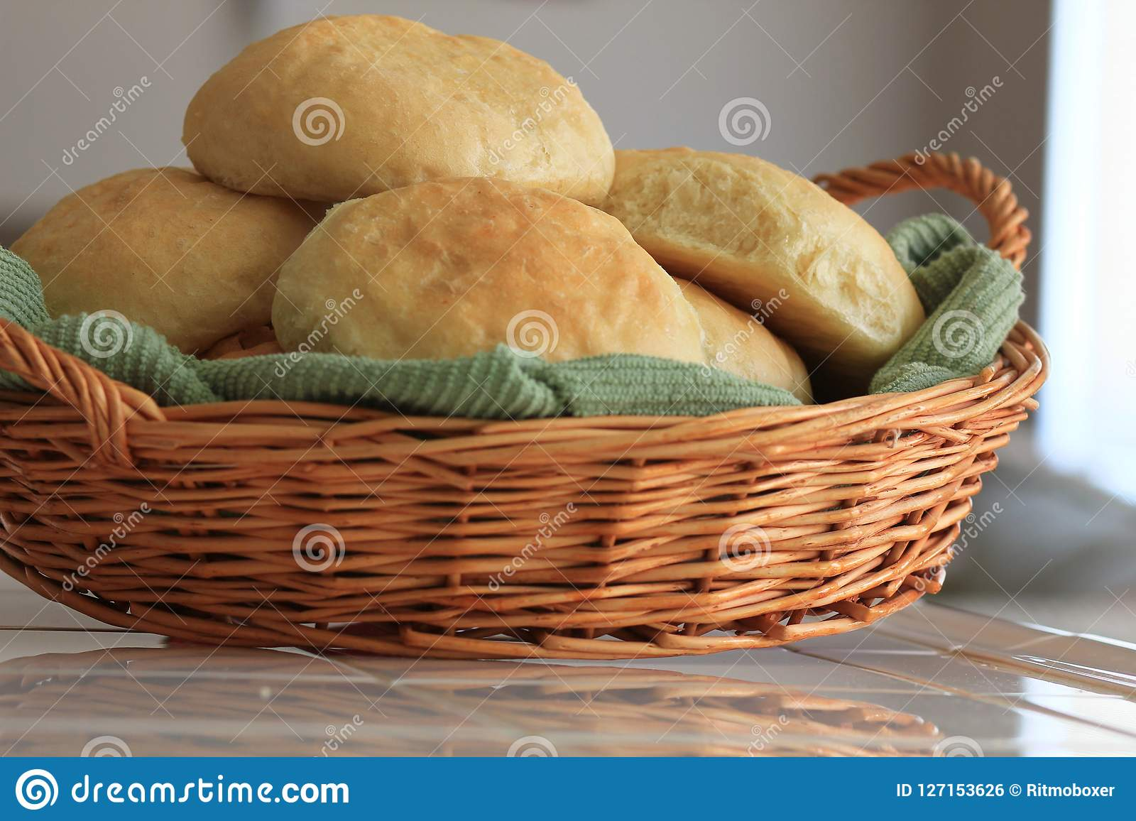 Freshly baked homemade yeast bread rolls resting in a wicker basket.