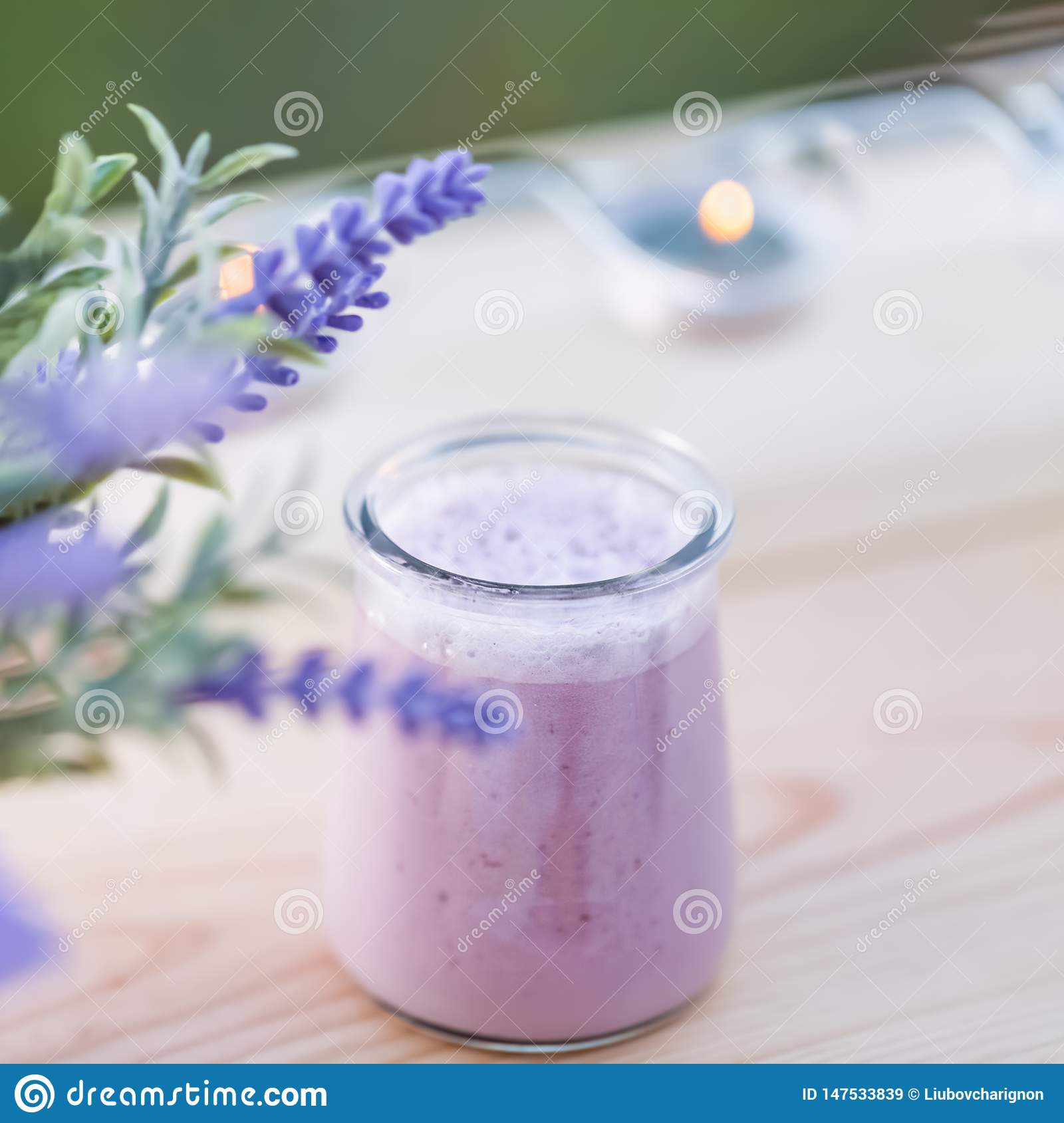 Homemade yogurt with blueberry in jars in an orchard in summertime. Evening light.