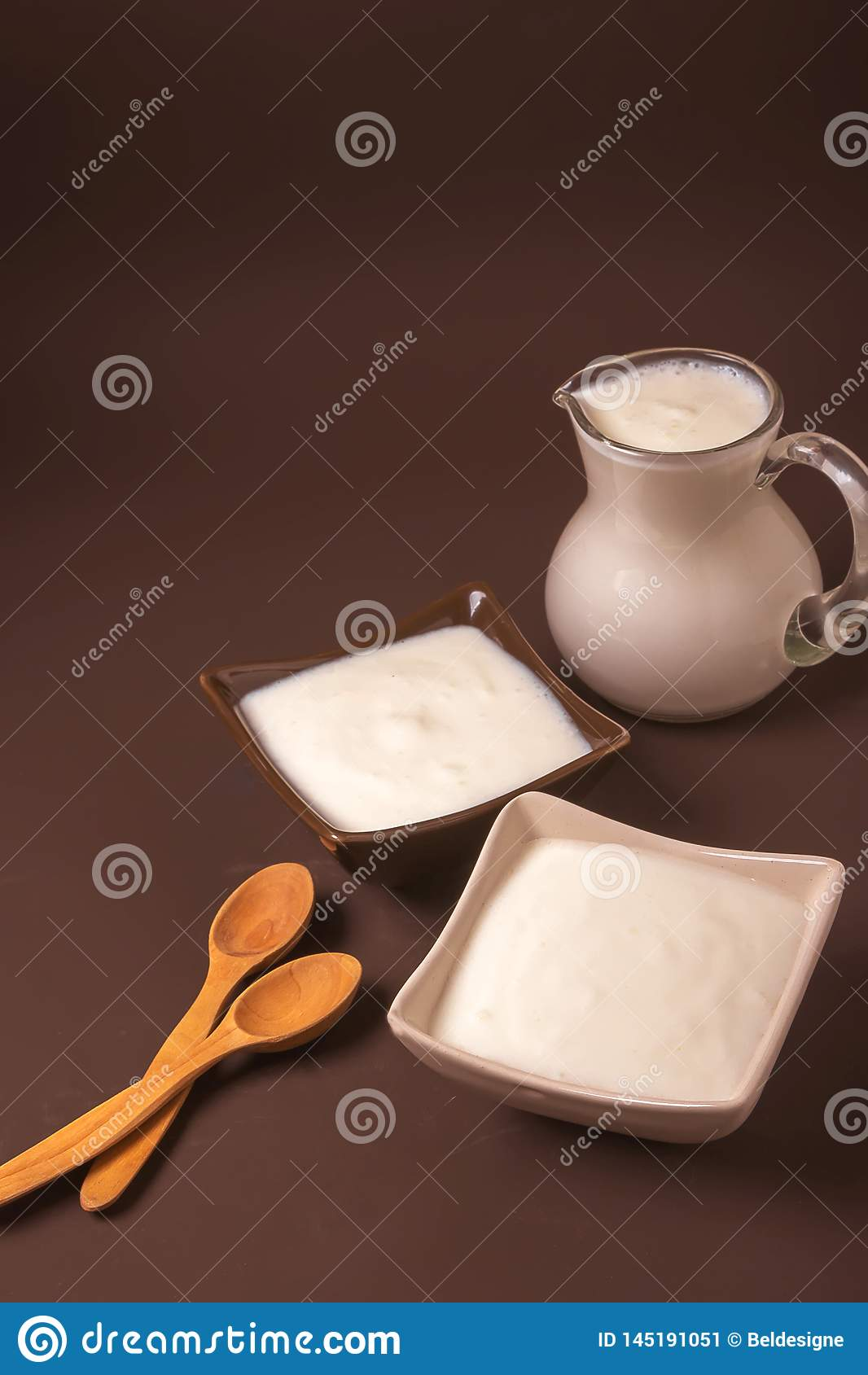 Homemade yogurt in ceramic square bowls, a jug brim full of yogurt behind the bowls. Healthy food from yogurt concept