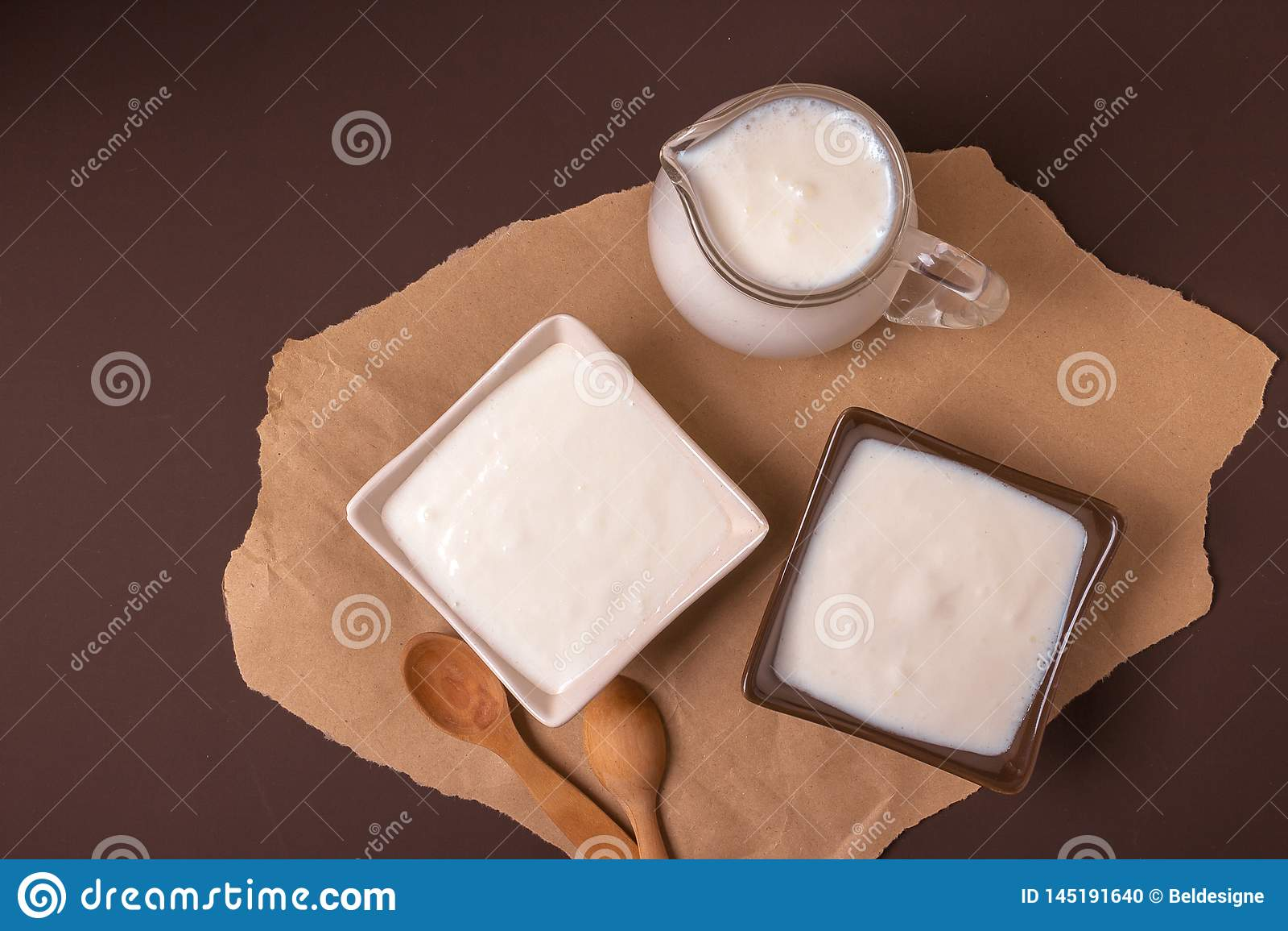 Homemade yogurt in ceramic square bowls, a jug brim full of yogurt behind the bowls. Healthy food from yogurt concept. Top view