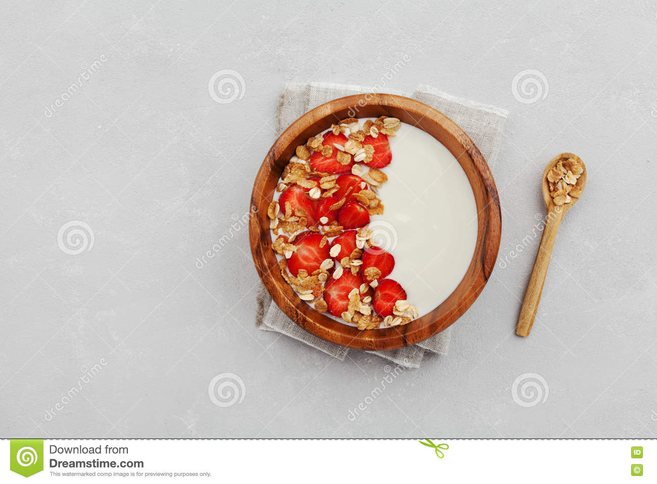 Homemade yogurt in wooden bowl with strawberry and granola or muesli on light table, healthy breakfast from above