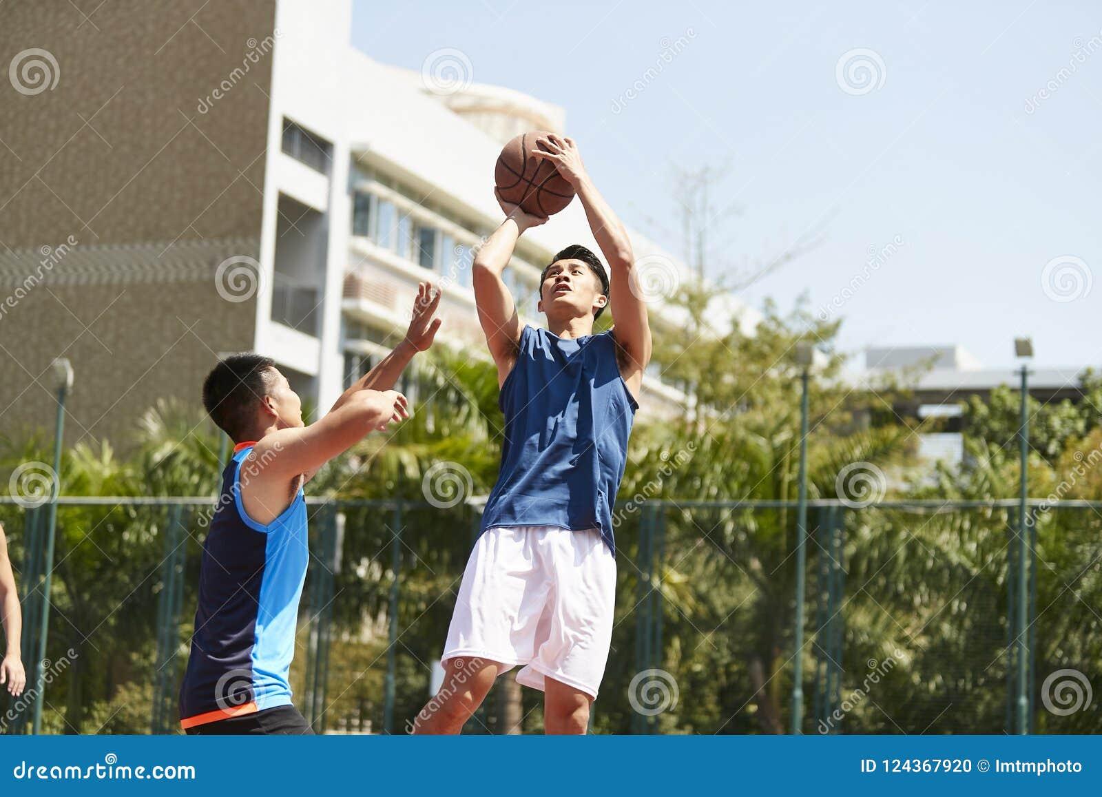 Homens asiáticos novos que jogam o basquetebol