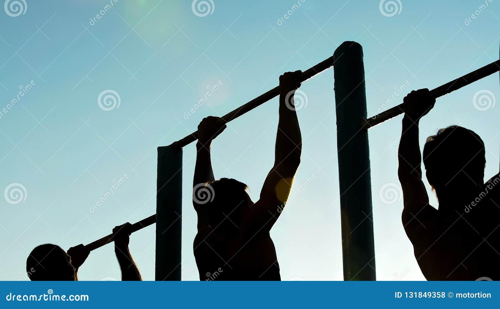 Homens atléticos que fazem tração-UPS nas barras do queixo-acima, preparando-se para a competição de esportes