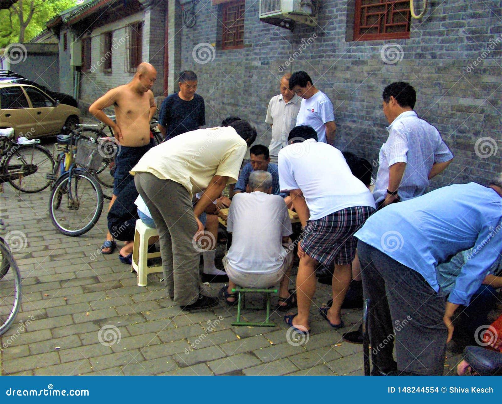 Homens chineses que jogam o majiang ao longo da rua Divertimento e entretenimento em China