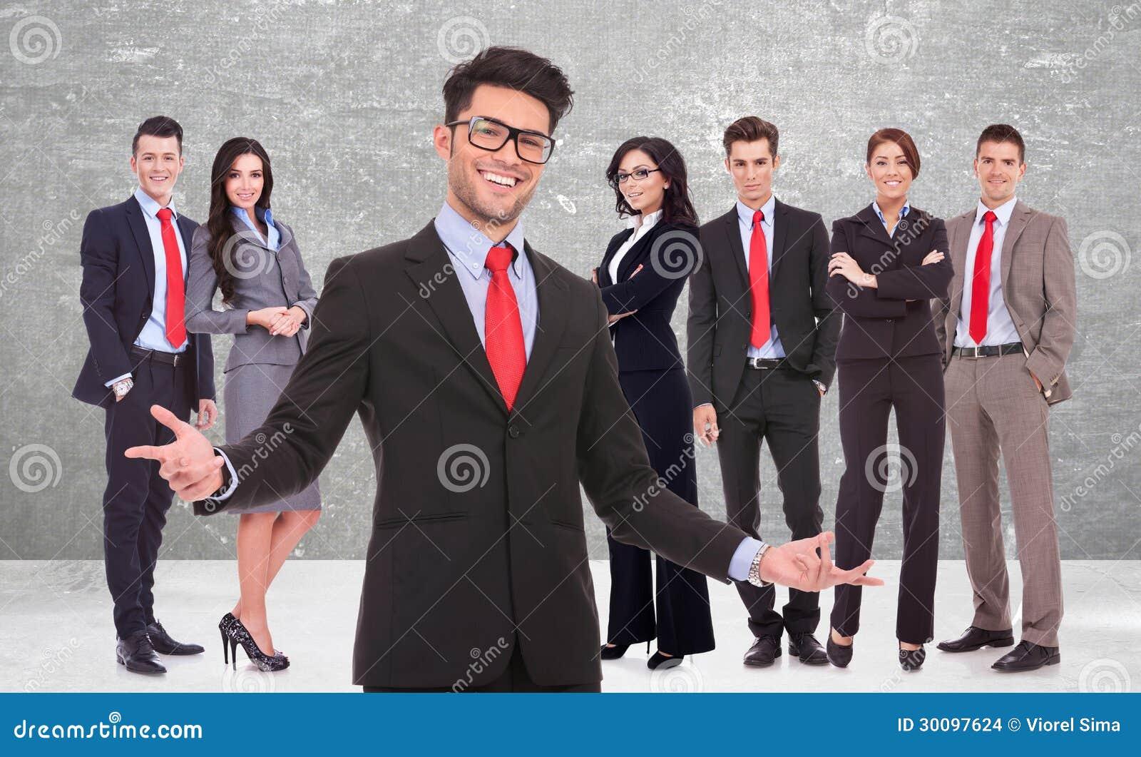 Homem de negócio que dá boas-vindas a lhe a sua equipe bem sucedida
