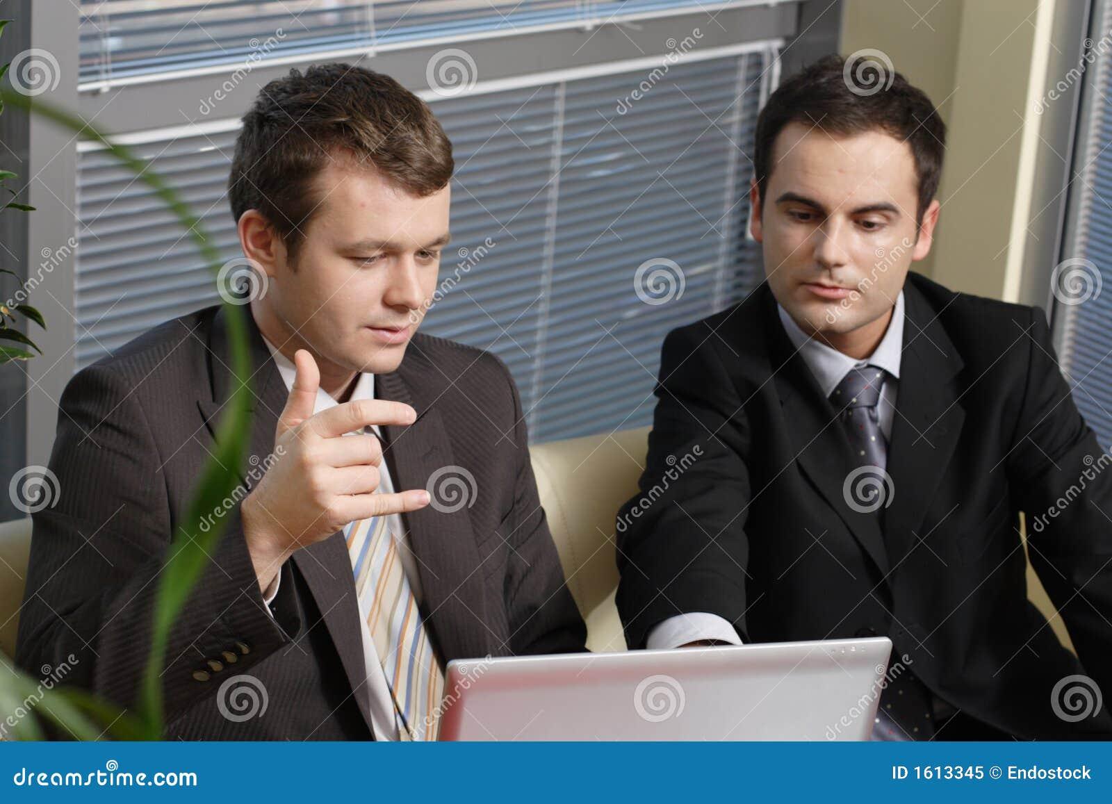 Homens de negócio novos que trabalham com latop no escritório