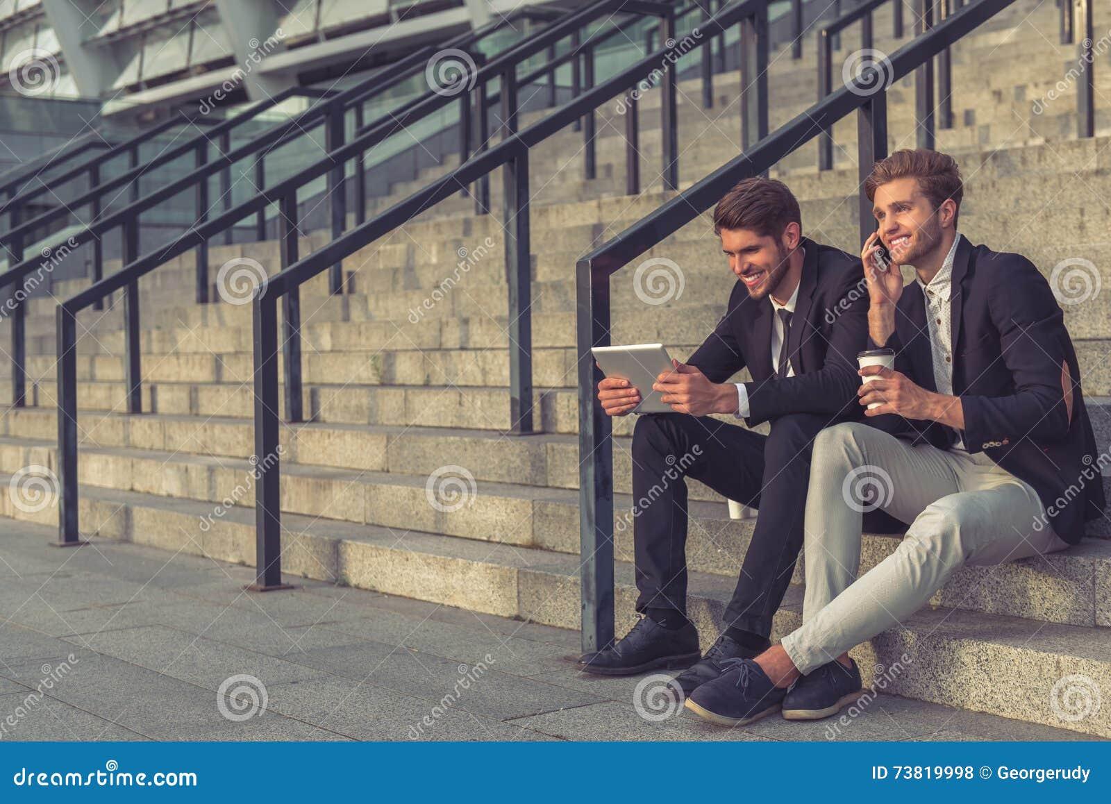 Homens de negócios novos consideráveis com dispositivo
