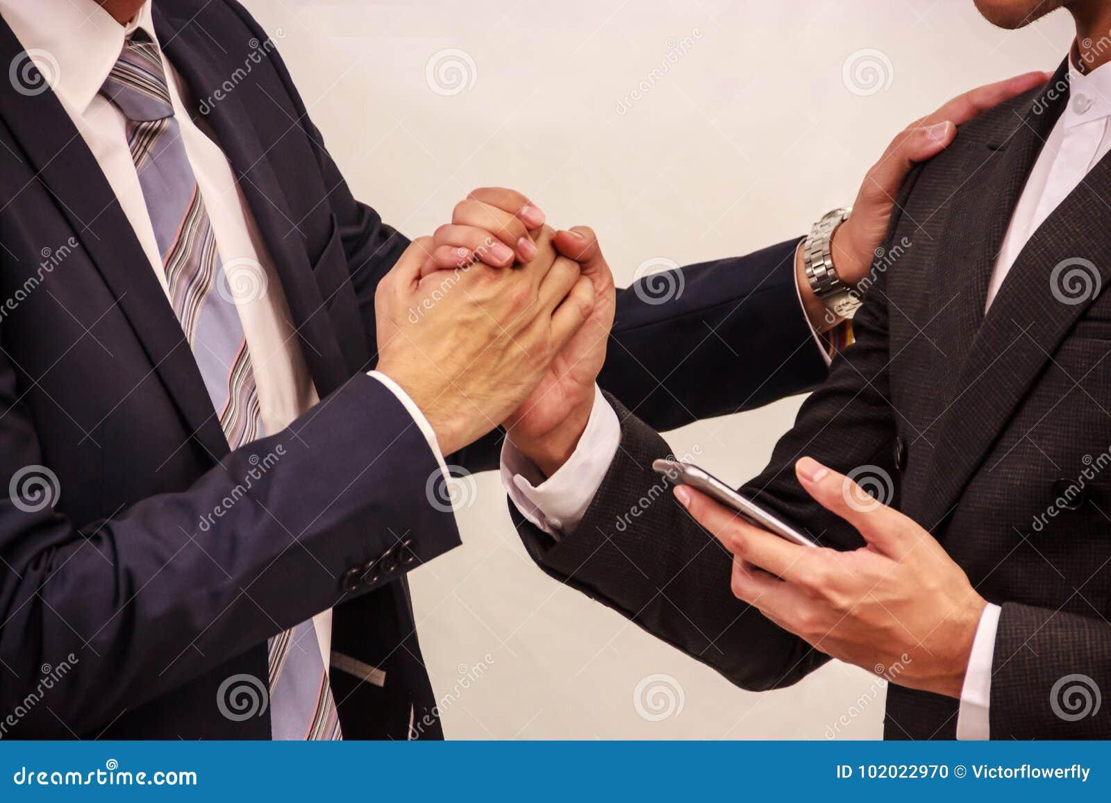 Homens de negócios que guardam a mão após o negócio confirmado no telefone esperto Ideia conceptual do sucesso, venda fechado, tr