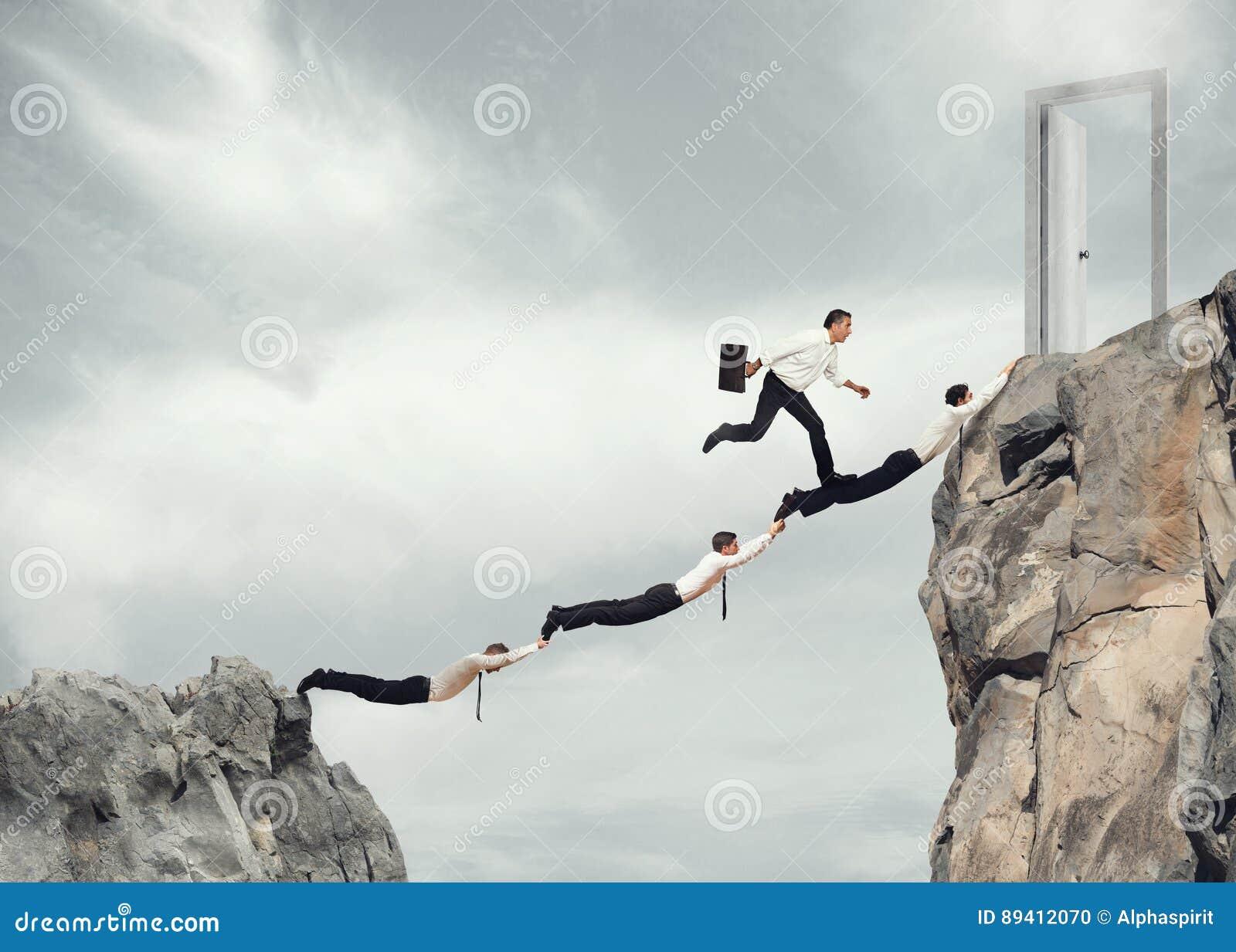 Homens de negócios que trabalham junto para alcançar uma porta