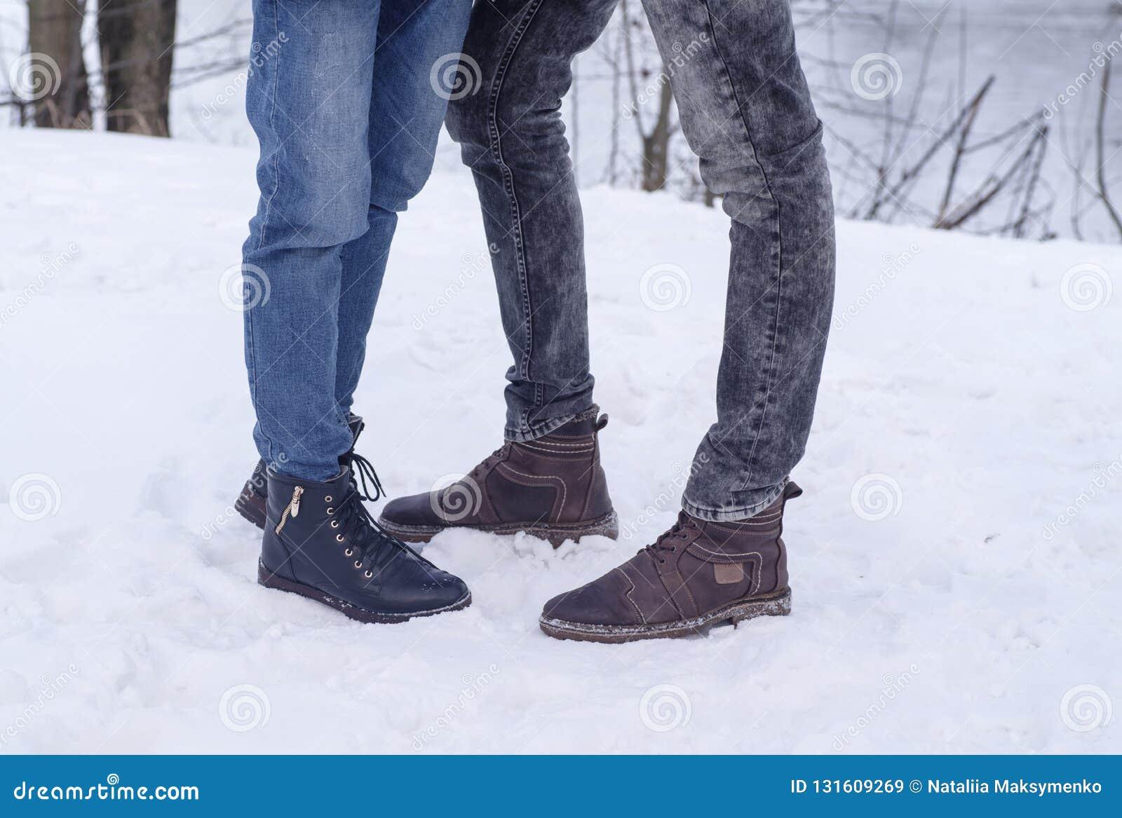 Homens e sapatas das mulheres no fundo de pedra snowal Fragmento de uma parede de uma pedra lascada
