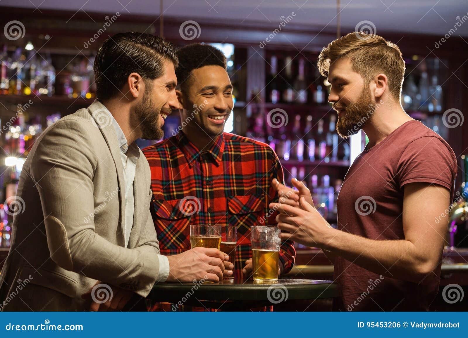 Homens felizes novos que bebem a cerveja e que falam no café