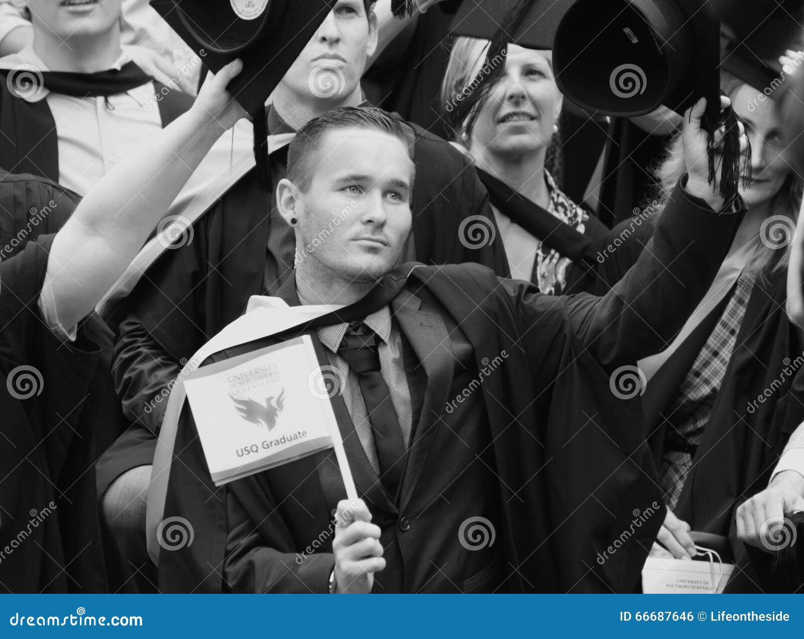 Homens novos & graduados orgulhosos das mulheres do dia de graduação da universidade de USQ