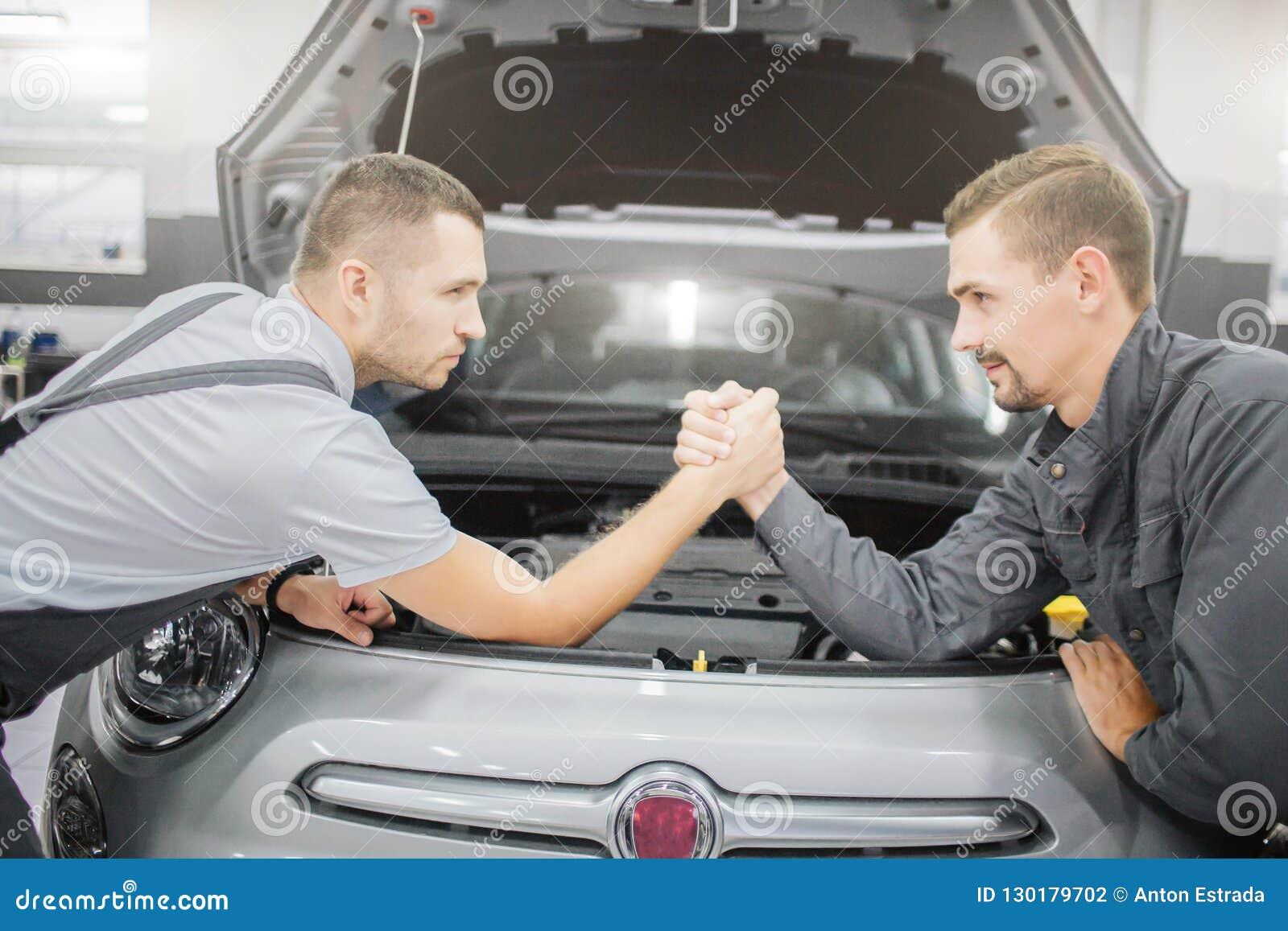Homens novos que fazem um acordo entre se Inclinam-se ao carro e guardam-se as mãos de cada um A parte dianteira do corpo de carr