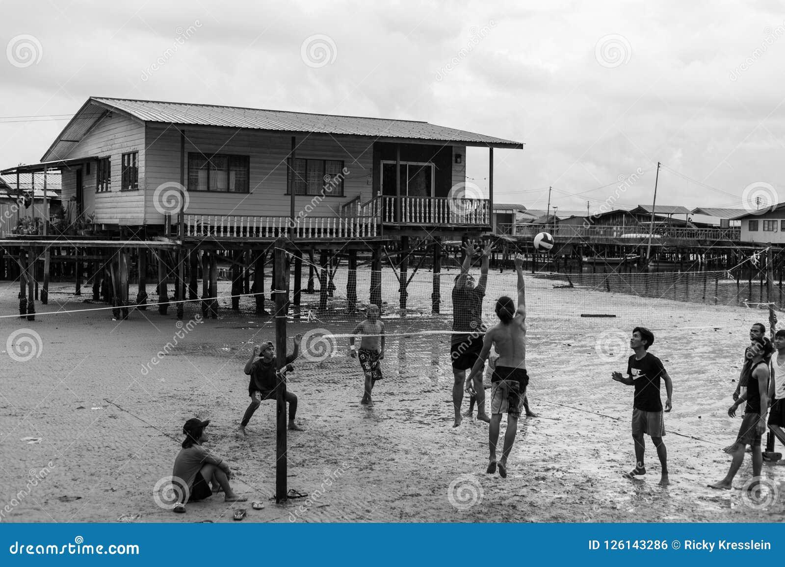 Homens novos que jogam a maré baixa Vill pobre residencial dos meninos do voleibol