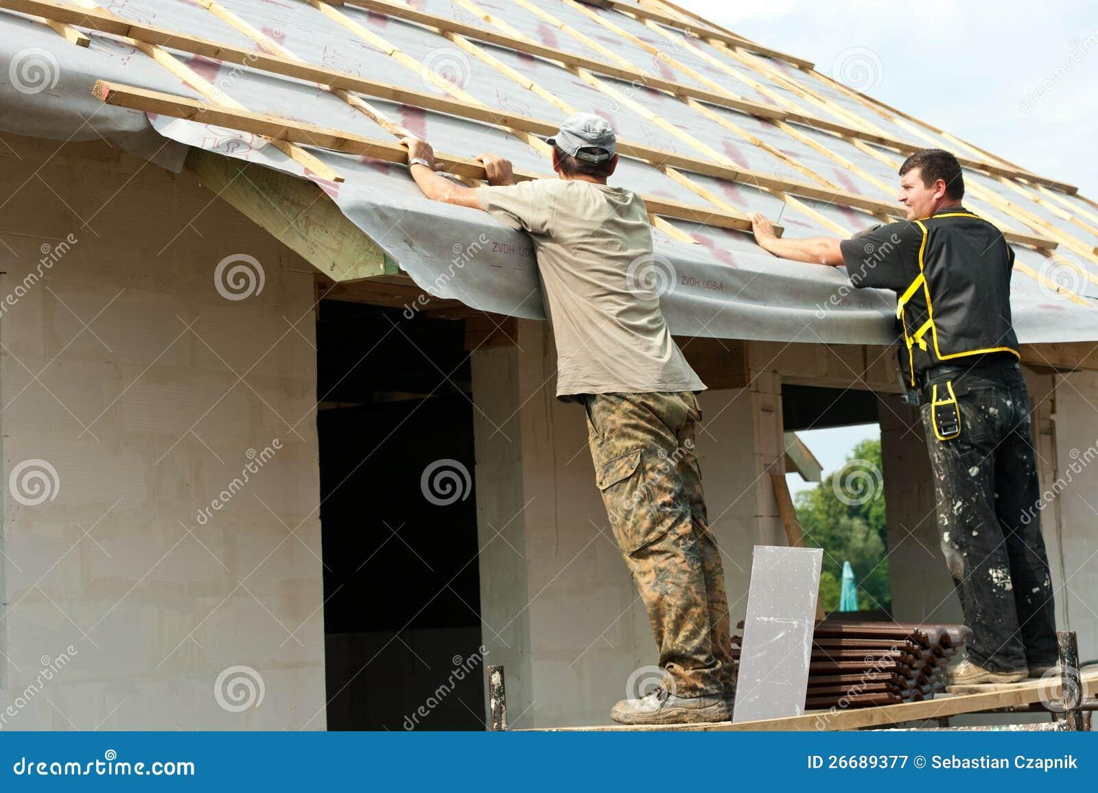 Homens que põr o telhado sobre uma casa